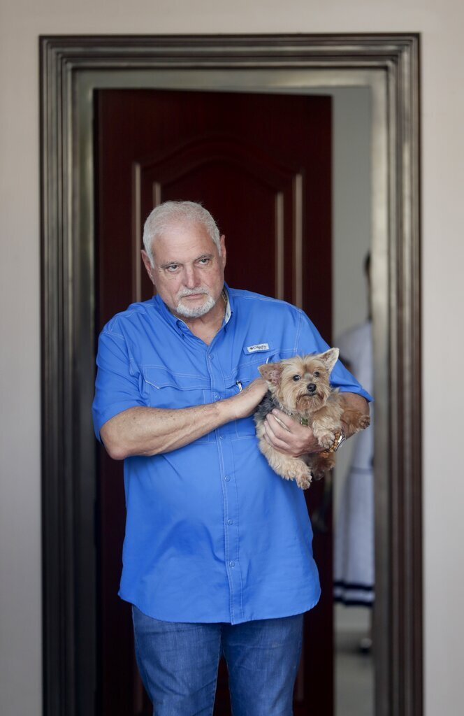Former Panamanian President Ricardo Martinelli holds a dog at his home in Panama City, Wednesday, June 12, 2019. A Panamanian court ordered that former President Martinelli to be transferred from jail to house arrest. (AP Photo/Arnulfo Franco)