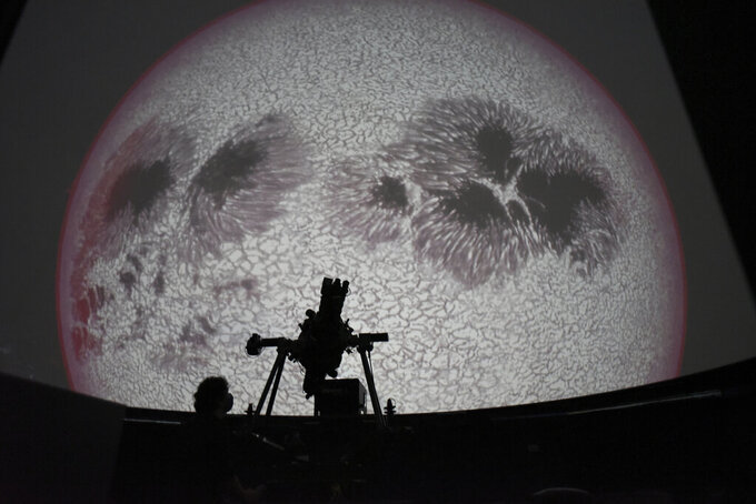 Researcher Ivannia Calvo, silhouetted against a solar satellite image, works inside the Solar Astronomical Observatory in San Jose, Costa Rica, Friday, April 30, 2021. Costa Rica approved a law creating a space agency on Feb. 18. (AP Photo/Carlos Gonzalez)