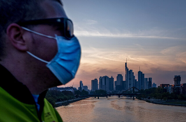 A man wears a face mask as he walks across the bridge over the river Main in Frankfurt, Germany, Wednesday, Sept. 30, 2020. (AP Photo/Michael Probst)