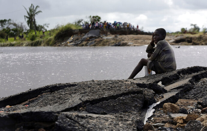 A young boy sits on the edge of a collapsed bridge in Nhamatanda, about 100km west of Beira, Thursday, March 21, 2019. A week after Cyclone Idai lashed southern Africa, flooding still raged Thursday as torrential rains caused a dam to overflow in Zimbabwe, threatening riverside populations. The confirmed death toll in Zimbabwe, neighboring Mozambique and Malawi surpassed 500, with hundreds more feared dead in towns and villages that were completely submerged. (AP Photo/Themba Hadebe)
