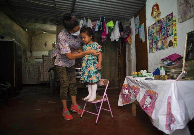 Elena Escalante helps her 3-year-old daughter Zaii prepare for a homespun beauty pageant in the Antimano neighborhood of Caracas, Venezuela, Friday, Feb. 5, 2021. Neighbors in the hillside barrio gathered for the carnival pageant tradition to select their child queen for the upcoming festivities.(AP Photo/Ariana Cubillos)