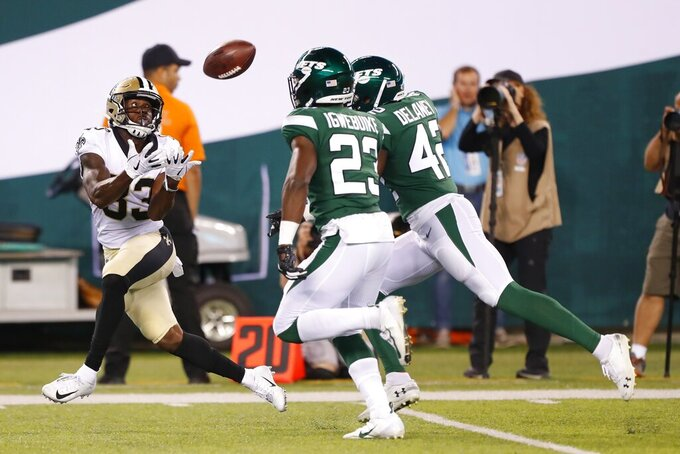 New Orleans Saints' Cyril Grayson (83) catches a pass in front of New York Jets' Godwin Igwebuike (23) and another defender during the second half of a preseason NFL football game Saturday, Aug. 24, 2019, in East Rutherford, N.J. (AP Photo/Noah K. Murray)