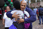 FILE— In this July 18, 2021 file photograph, Boston mayoral candidate John Barros is embraced prior to the start of the Roxbury Unity Parade in Boston's Roxbury neighborhood. With Boston's preliminary mayoral election just a month off, voters are on the verge of making a historic decision by narrowing the field of five major candidates, all of whom are people of color. Since it first started electing mayors nearly 200 years ago, Boston has only tapped white men to lead the city — a streak certain to end this year, a reflection in part of the city's changing demographics. (AP Photo/Steven Senne, File)