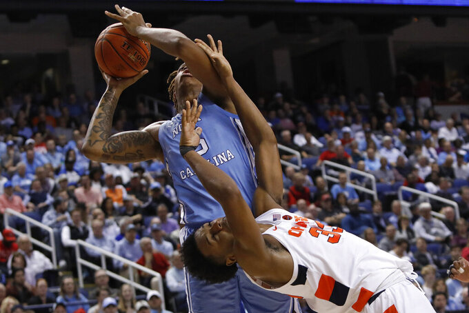 Syracuse forward Elijah Hughes (33) leans over to reach for the ball with North Carolina forward Armando Bacot during the first half of an NCAA college basketball game at the Atlantic Coast Conference tournament in Greensboro, N.C., Wednesday, March 11, 2020. (AP Photo/Ben McKeown)