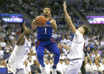 Kansas guard Devon Dotson (1) handles the ball inside a TCU center Kevin Samuel (21) and guard Francisco Farabello (3) defend during the first half of an NCAA college basketball game, Saturday, Feb. 8, 2020, in Fort Worth, Texas. (AP Photo/Ron Jenkins)