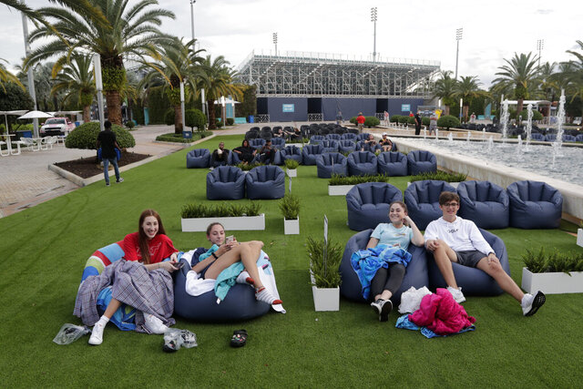 FILE - In this Thursday, June 18, 2020 file photo, people sit outdoors to watch a movie as part of a program offered by the Miami Dolphins at Hard Rock Stadium during the coronavirus pandemic in Miami Gardens, Fla. Elected officials such as Florida's governor have argued against reimposing restrictions, saying many of the newly infected are young and otherwise healthy. But younger people, too, face the possibility of severe infection and death. And authorities worry that older, more vulnerable people could be next. (AP Photo/Lynne Sladky)