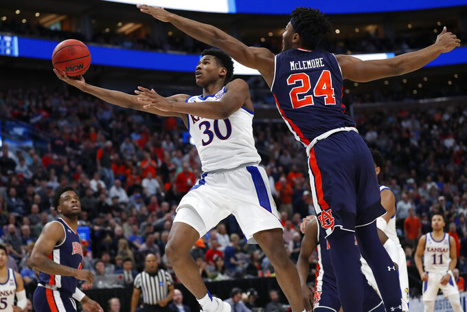 Kansas guard Ochai Agbaji (30) drives to the basket against Auburn forward Anfernee McLemore (24) during the second half of a second-round game in the NCAA men's college basketball tournament Saturday, March 23, 2019, in Salt Lake City. (AP Photo/Jeff Swinger)
