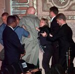 FILE - In this Nov. 30, 1999, file photo, two anti-World Trade Organization protesters, center, are escorted out of the Paramount Theatre in downtown Seattle by authorities after they stepped onstage and began speaking into the microphone.   Saturday, Nov. 30, 2019 marks 20 years since tens of thousands of protesters converged on Seattle and disrupted a major meeting of the World Trade Organization. The protesters' message was amplified not just by their vast numbers but by the response of overwhelmed police, who fired tear gas and plastic bullets and arrested nearly 600 people. Two decades later, many of their causes are still relevant.  (AP Photo/Elaine Thompson, File)
