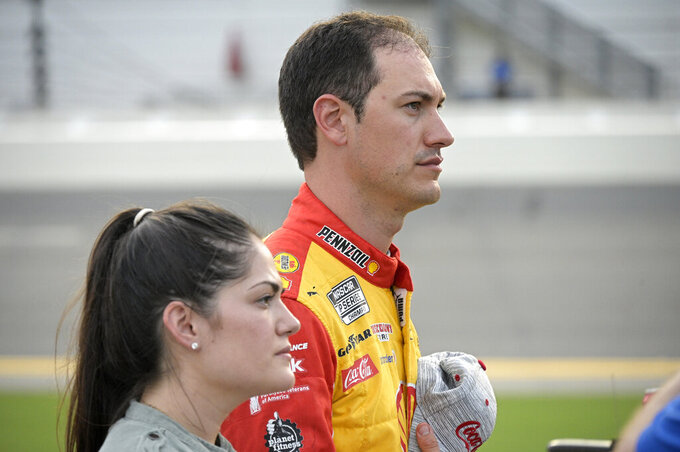 Driver Joey Logano, right, stands next to his vehicle with his wife Brittany Baca on pit road before a NASCAR Cup Series auto race at Daytona International Speedway, Saturday, Aug. 28, 2021, in Daytona Beach, Fla. (AP Photo/Phelan M. Ebenhack)