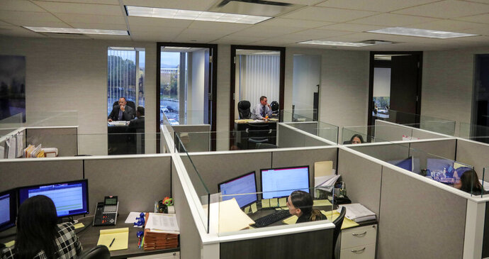 This Tuesday, Oct. 29, 2019, photo taken at the law firm of Slater, Slater and Schulman, shows lawyers Linc Leder, top left, and Michael Werner, top right, in their offices, while paralegals work in their cubicles, in Melville, N.Y. Attorney Adam Slater said since New York state opened its one-year window allowing sex abuse suits with no statute of limitations, his firm has signed up nearly 300 new clients and hired a half-dozen new paralegals to field calls. (AP Photo/Bebeto Matthews)
