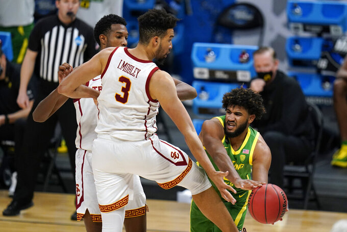 Oregon guard LJ Figueroa, right, passes around Southern California forward Isaiah Mobley (3) during the second half of a Sweet 16 game in the NCAA men's college basketball tournament at Bankers Life Fieldhouse, Sunday, March 28, 2021, in Indianapolis. (AP Photo/Jeff Roberson)