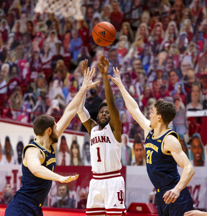 Indiana guard Aljami Durham (1) tries to score with a three-point shot during the second half of an NCAA college basketball game against Michigan, Saturday, Feb. 27, 2021, in Bloomington, Ind. (AP Photo/Doug McSchooler)