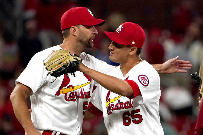 St. Louis Cardinals' Giovanny Gallegos (65) and teammate Adam Wainwright celebrate a 5-4 victory over the Los Angeles Dodgers in a baseball game Wednesday, Sept. 8, 2021, in St. Louis. (AP Photo/Jeff Roberson)