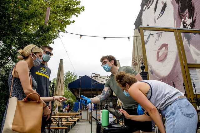 A large Elizabeth Taylor mural is visible behind Steven Scammacca, center right, as he checks IDs and Amy Symonds as she works at Dacha Beer Garden which has opened in the Shaw neighborhood in Washington, Friday, May 29, 2020, as the District of Columbia gradually loosens stay-at-home rules that have been in place since March 25 because of the pandemic and allows restaurants to resume outdoor dining. (AP Photo/Andrew Harnik)