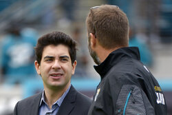 FILE - In this Dec. 15, 2013, file photo, Jacksonville Jaguars senior vice president Tony Khan, left, talks with an unidentified person prior to an NFL football game against the Buffalo Bills in Jacksonville, Fla. Disgruntled Jacksonville Jaguars defensive end Yannick Ngakoue goaded minority owner Tony Khan into a Twitter exchange Monday, April 20, 2020, in hopes of escalating his public trade demand. It may have backfired.(AP Photo/Phelan M. Ebenhack, File)