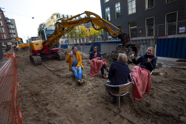 People enjoy a beer on an improvised beach terrace during road construction works outside a bar in Amsterdam, Netherlands, Friday, Oct. 23, 2020. Dutch bars and restaurants were closed as of last week as part of a