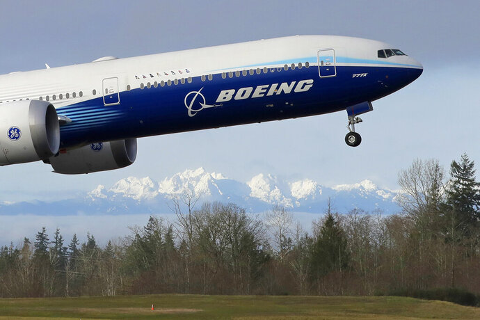 FILE - In this Jan. 25, 2020, file photo a Boeing 777X airplane takes off on its first flight with the Olympic Mountains in the background at Paine Field in Everett, Wash. Boeing is reporting another huge loss, this one because of a setback to its 777X widebody jetliner. Boeing said Wednesday, Jan. 27, 2021, it lost $8.4 billion in the fourth quarter on weaker demand for planes during the pandemic. (AP Photo/Ted S. Warren, File)
