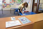 Reception teacher Elizabeth Dockry cleans her classroom as measures are taken to prevent the transmission of coronavirus before the possible reopening of Lostock Hall Primary school in Poynton near Manchester, England, Wednesday May 20, 2020. (AP Photo/Jon Super)