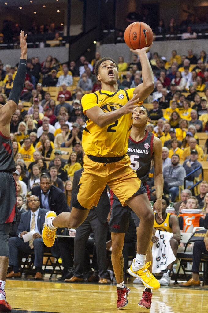 Missouri's Tray Jackson, left, shoots in front of Arkansas' Jalen Harris, right, during the second half of an NCAA college basketball game Saturday, Feb. 8, 2020, in Columbia, Mo. Missouri beat Arkansas 83-79 in overtime. (AP Photo/L.G. Patterson)