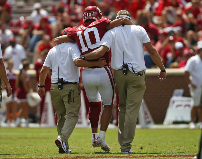 Oklahoma quarterback Austin Kendall (10) is helped off the field after an injury in the second half of an NCAA college football game against Florida Atlantic in Norman, Okla., Saturday, Sept. 1, 2018. (AP Photo/Sue Ogrocki)