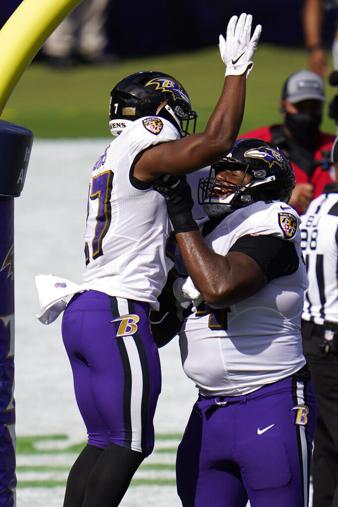 Baltimore Ravens offensive guard Tyre Phillips (74) lifts running back J.K. Dobbins (27) after Dobbins scored a touchdown, during the second half of an NFL football game, Sunday, Sept. 13, 2020, in Baltimore, MD. (AP Photo/Julio Cortez)