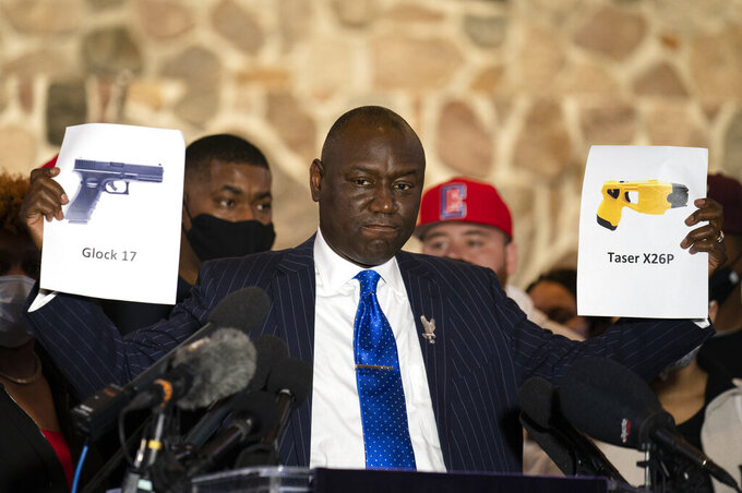 FILE - In this Thursday, April 15, 2021 file photo, attorney Ben Crump, representing the family of Daunte Wright, holds up images depicting an X26P Taser and a Glock 17 handgun during a news conference at New Salem Missionary Baptist Church in Minneapolis. (AP Photo/John Minchillo)