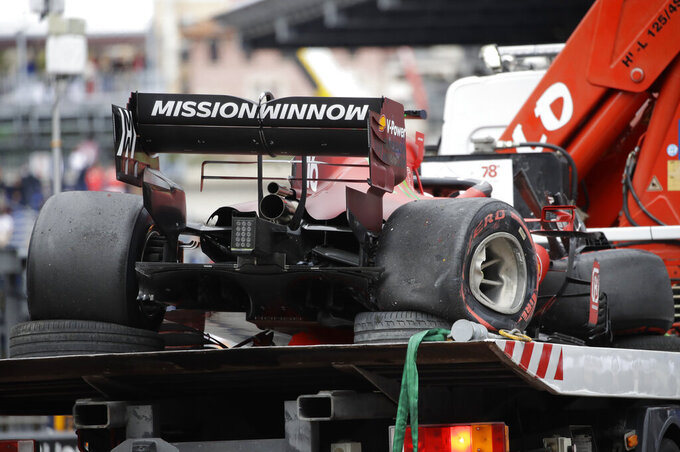 The car of Ferrari driver Charles Leclerc of Monaco is taken off the track after a crash during the qualifying session at the Monaco racetrack, in Monaco, Saturday, May 22, 2021. The Formula One race will take place on Sunday with Ferrari driver Charles Leclerc of Monaco in pole position. (AP Photo/Luca Bruno)