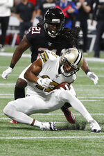 New Orleans Saints wide receiver Michael Thomas (13) makes the catch ahead of Atlanta Falcons cornerback Desmond Trufant (21) makes during the first half of an NFL football game, Thursday, Nov. 28, 2019, in Atlanta. (AP Photo/John Bazemore)