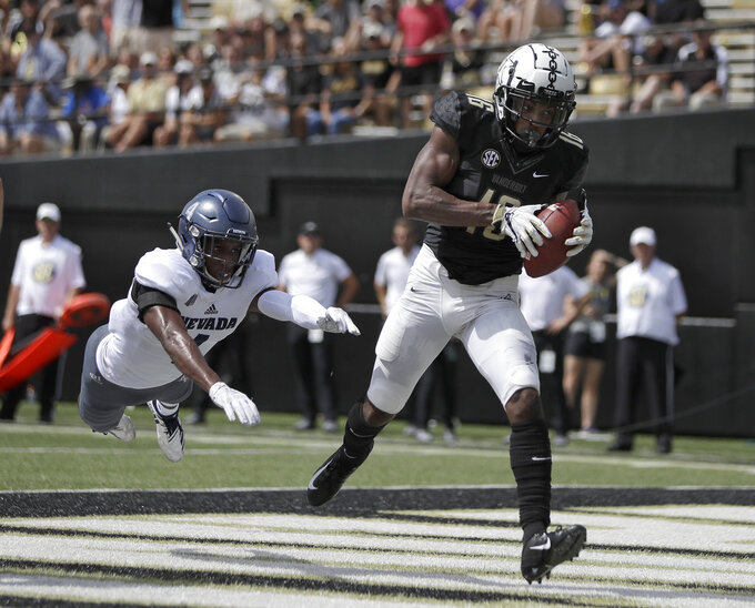 Vanderbilt wide receiver Kalija Lipscomb (16) catches a 2-yard touchdown pass ahead of Nevada defensive back EJ Muhammad (4) in the first half of an NCAA college football game Saturday, Sept. 8, 2018, in Nashville, Tenn. (AP Photo/Mark Humphrey)