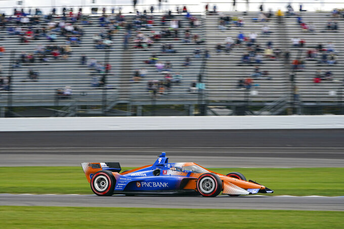 Scott Dixon, of New Zealand, drives past a stand with fans during an IndyCar auto race at Indianapolis Motor Speedway in Indianapolis, Friday, Oct. 2, 2020. The Speedway offered 10,000 tickets for fans to attend. (AP Photo/Michael Conroy)