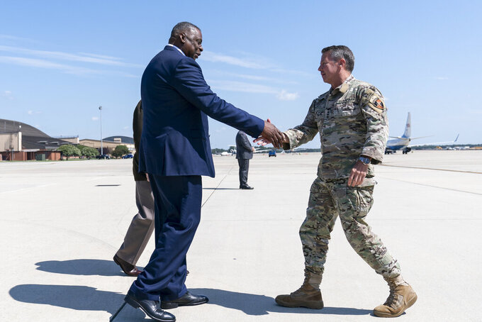 Secretary of Defense Lloyd Austin, left, greets U.S. Army Gen. Scott Miller, the former top U.S. commander in Afghanistan, upon his return Wednesday, July 14, 2021, at Andrews Air Force Base, Md. (AP Photo/Alex Brandon, Pool)