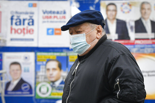 A man wearing a mask for protection against the COVID-19 infection walks by electoral posters in Bucharest, Romania, Thursday, Dec. 3, 2020. Romania will hold parliamentary elections on Sunday Dec. 6. (AP Photo/Andreea Alexandru)
