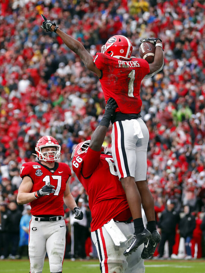 Georgia wide receiver George Pickens (1) celebrates with offensive lineman Solomon Kindley (66) after catching a touchdown on a pass from quarterback Jake Fromm (17) during the first half of an NCAA college football game against Texas A&M, Saturday, Nov. 23, 2019, in Athens, Ga. (AP Photo/John Bazemore)