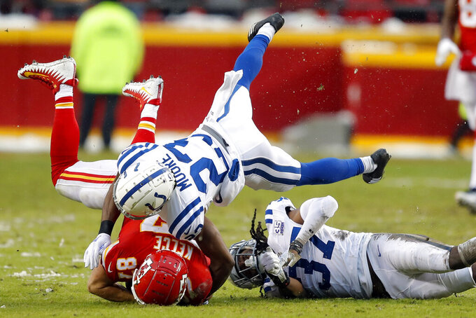 Indianapolis Colts cornerback Kenny Moore (23) tackles Kansas City Chiefs tight end Travis Kelce (87) next to defensive back J.J. Wilcox (37) during the first half of an NFL divisional football playoff game in Kansas City, Mo., Saturday, Jan. 12, 2019. (AP Photo/Charlie Neibergall)