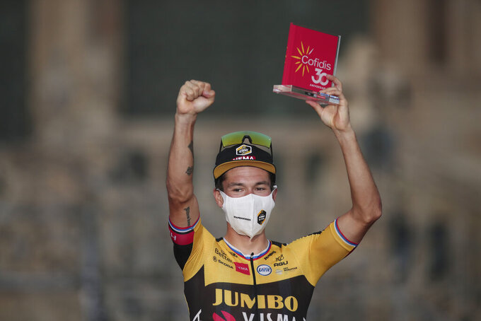 Primoz Roglic celebrates with the trophy after winning the Vuelta Cycling race in Santiago, Spain, Sunday, Sept. 5, 2021. (AP Photo/Luis Vieira)