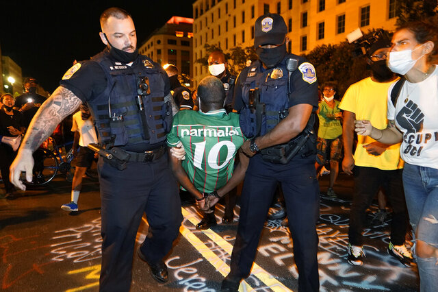Metropolitan Police carry away a handcuffed protestor along a section of 16th Street, Northwest, renamed Black Lives Matter Plaza, Thursday night , Aug. 27, 2020, in Washington, after President Donald Trump had finished delivering his acceptance speech from the White House South Lawn. (AP Photo/Julio Cortez)