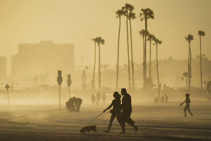 FILE - In this April 18, 2021, file photo, people walk on a beach path as evening winds kick up sand in Long Beach, Calif. California's population has declined for the first time in its history. State officials announced Friday, May 7, that the nation's most populous state lost 182,083 people in 2020. California's population is now just under 39.5 million. (AP Photo/Ashley Landis, File)