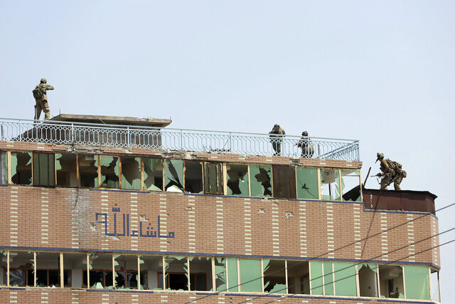 Afghan security personnel take position on the top of a building where insurgents were hiding, in the city of Jalalabad, east of Kabul, Afghanistan, Monday, Aug. 3, 2020. An Islamic State group attack on a prison in eastern Afghanistan holding hundreds of its members raged on Monday after killing people in fighting overnight, a local official said. (AP Photo/Rahmat Gul)