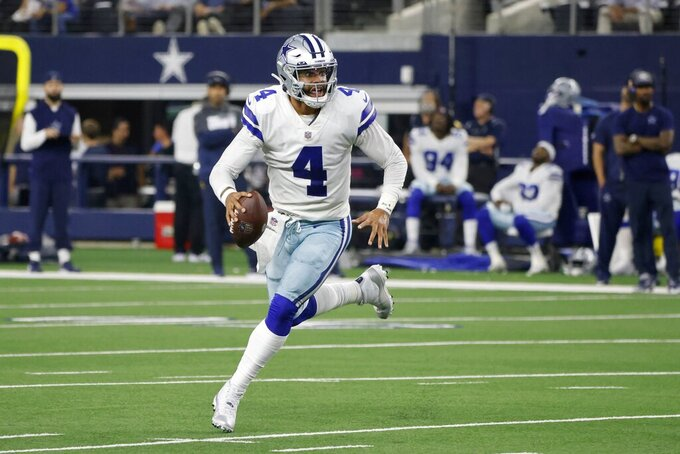 Dallas Cowboys quarterback Dak Prescott (4) runs the ball out of the pocket before throwing a pass in the first half of an NFL football game against the Philadelphia Eagles in Arlington, Texas, Monday, Sept. 27, 2021. (AP Photo/Michael Ainsworth)