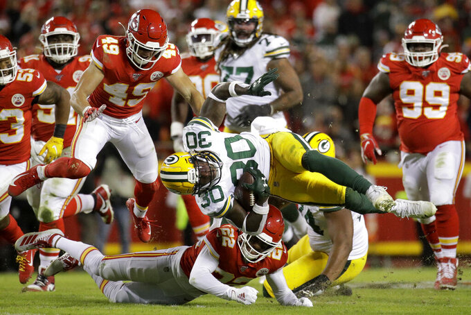 Green Bay Packers running back Jamaal Williams (30) is tackled by Kansas City Chiefs safety Juan Thornhill (22), as safety Daniel Sorensen (49) jumps during the second half of an NFL football game in Kansas City, Mo., Sunday, Oct. 27, 2019. (AP Photo/Charlie Riedel)