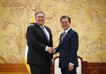 U.S. Secretary of State Mike Pompeo, left, poses with South Korean President Moon Jae-in for a photo during a bilateral meeting at the presidential Blue House in Seoul, South Korea Thursday, June 14, 2018. (Kim Hong-ji/Pool Photo via AP)