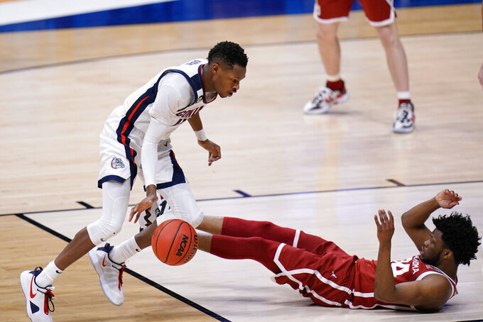 Oklahoma guard Elijah Harkless, right, hits the floor after fouling Gonzaga guard Joel Ayayi in the first half of a college basketball game in the second round of the NCAA tournament at Hinkle Fieldhouse in Indianapolis, Monday, March 22, 2021. (AP Photo/AJ Mast)