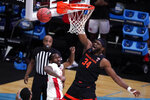 Oregon State forward Rodrigue Andela (34) misses dunk ahead of Houston guard DeJon Jarreau, left, during the first half of an Elite 8 game in the NCAA men's college basketball tournament at Lucas Oil Stadium, Monday, March 29, 2021, in Indianapolis. (AP Photo/Michael Conroy)