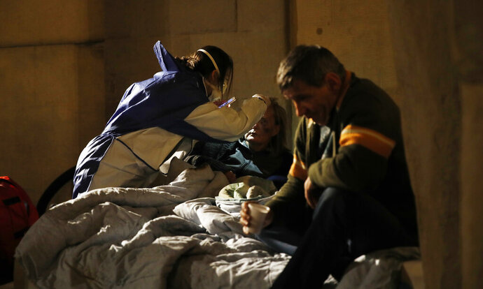 A volunteer nurse wearing a mask tends to an homeless in Milan, early Wednesday, March 25, 2020. The new coronavirus causes mild or moderate symptoms for most people, but for some, especially older adults and people with existing health problems, it can cause more severe illness or deaths. (AP Photo/Antonio Calanni)