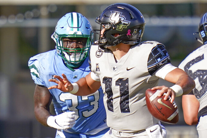 Tulane linebacker Kevin Henry, left, pressures Central Florida quarterback Dillon Gabriel (11) who looks for a receiver during the second half of an NCAA college football game Saturday, Oct. 24, 2020, in Orlando, Fla. (AP Photo/John Raoux)
