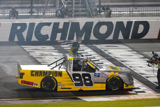 Grant Enfinger gets out of his car as he celebrates after winning a NASCAR Truck Series auto race Thursday, Sept. 10, 2020, in Richmond, Va. (AP Photo/Steve Helber)