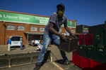 A worker loads alcoholic beverages outside the Sam Liquor Store in Thokoza township, near Johannesburg, South Africa, Monday, June 1, 2020.  Liquor stores have reopened Monday after being closed for over two months under lockdown restrictions in a bid to prevent the spread of coronavirus.(AP Photo/Themba Hadebe)