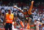 FILE - United States' Lex Gillette, right, jumps as his escort, left, looks on during the men's Triple Jump F11 at the Beijing 2008 Paralympic Games in Beijing, China, in this Friday, Sept. 12, 2008, file photo. Blind long jumper Lex Gillette is chasing after Paralympic gold after four straight silver medals. (AP Photo/Eugene Hoshiko, File)