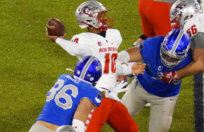 New Mexico quarterback Trae Hall, center, unloads a pass under pressure from Air Force defensive end Michael Purcell, front, and defensive tackle George Silvanic during the first half of an NCAA college football game Friday, Nov. 20, 2020, at Air Force Academy, Colo. (AP Photo/David Zalubowski)