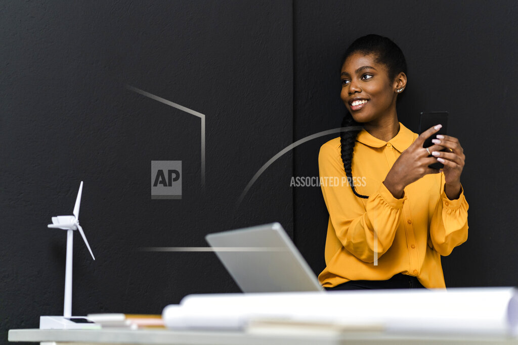 Smiling businesswoman holding mobile phone while looking away in studio
